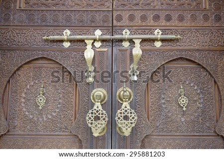 Moroccan style door latch on an intricately carved wooden door - stock photo