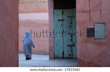 Moroccan woman in djellaba walking in Marrakesh's medina - stock photo