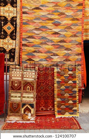 Morocco  Marrakesh Essaouira Colorful Berber carpets for sale hanging in front of a shop in the historic medina - stock photo