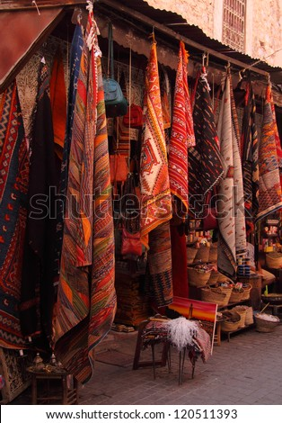 Morocco, Marrakesh, Typical colourful woollen rugs and handy-craft articles on display in the Medina souk. - stock photo