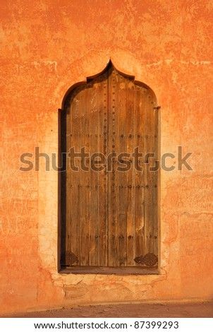 Morocco Marrakesh typical old arabesque door surrounded by rustic terracotta colored wall - Menara Pavilion - stock photo