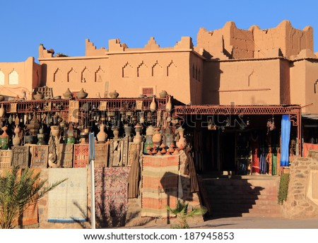 Morocco, Ouarzazate in the High Atlas Mountain range - traditional crafts on display in front of an adobe built building. - stock photo