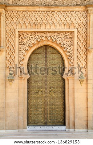 Morocco, Rabat, typical old arabesque intricate engraved brass door and surround in sandstone  sculpted in detailed Islamic design - stock photo