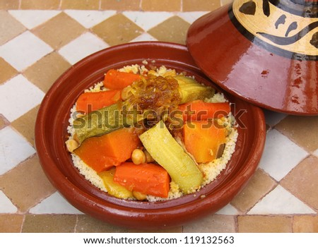 "Morocco Traditional ""Berber"" tajine and couscous - Mixed vegetables, stewed beef with caramelized onions and saffron on a bed of couscous in a typical tajine dish. - stock photo"