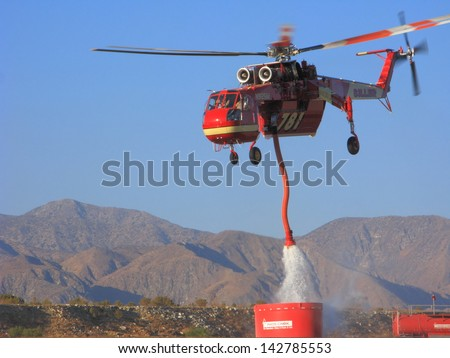 MORONGO, US - JUNE 16: Ericcson Sky Crane, also known as Sykorsky S-640, refills air tanker with fire retardant during Hathaway fire in San Bernardino National Forest in Morongo on June 16, 2013. - stock photo