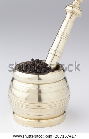 Mortar and pestle made of brass with Black Pepper. - stock photo
