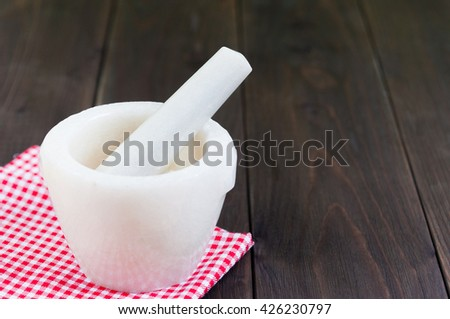 Mortar and pestle of marble on a old wooden board - stock photo