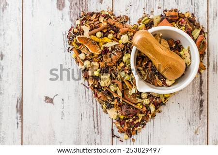 Mortar and pestle set with herbal tea designed as heart shape - stock photo