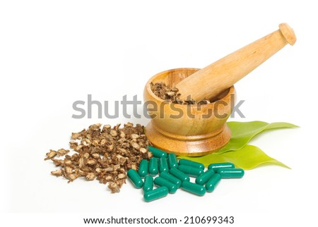 Mortar and pestle with herb capsules  - stock photo