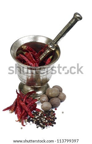 Mortar and pestle with some spices mortar and pestle and some spices isolated in white background. The spices in the background are red peppers, four season pepper and nutmeg - stock photo