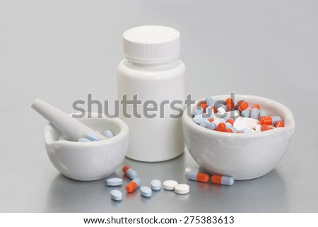 Mortar and pestles with colorful capsules and bottle. - stock photo