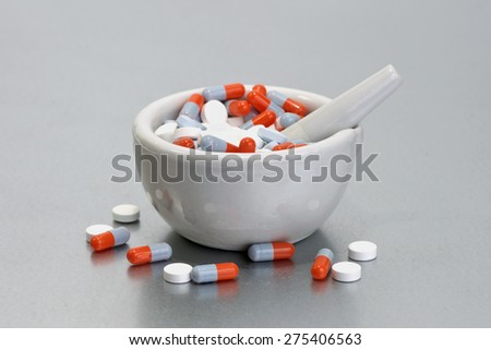 Mortar and pestles with colorful capsules on metal tray. - stock photo