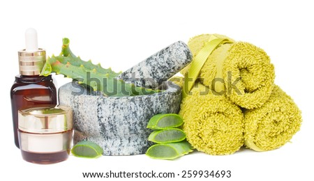 mortar with  fresh aloe vera slices, towels and creams  isolated on white background - stock photo