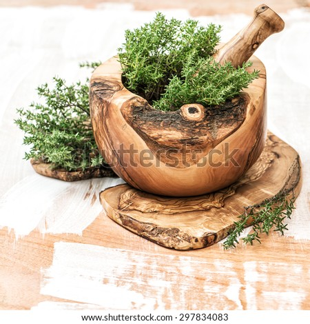 Mortar with fresh thyme herb. Olive wood kitchen tools. Healthy food ingredients - stock photo