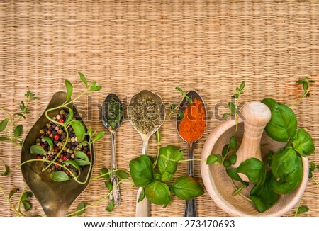 mortar with herbs and spices on a straw mat background - stock photo