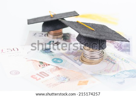 Mortarboard on coins and pound sterling banknotes close up  - stock photo