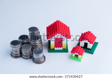 Mortgage concept by three model house with coin towers - stock photo