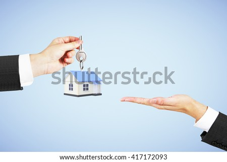 Mortgage concept with businessman handing house with key to another man on blue background - stock photo