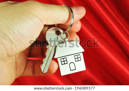 Mortgage concept with hand holding key and house-shaped keyring against red background  - stock photo