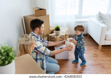 mortgage, people, housing, moving and real estate concept - happy family with boxes playing ball at new home - stock photo
