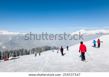MORZINE, FRANCE - FEBRUARY 07, 2015: Skiers and snowboarders on La Combe piste in Morzine resort, part of the Portes du Soleil ski area. - stock photo