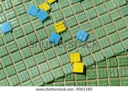 Mosaic tiles on sheet with a few random tiles on top - stock photo