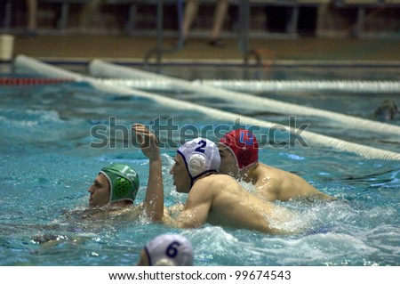 MOSCOW - APRIL  6: Unidentified player in white defends a gate during a game Dynamo(white) vs Sintez (green) of waterpolo Championship of Russia on April 6, 2012 Moscow, Russia. Sintez won 11:10 - stock photo