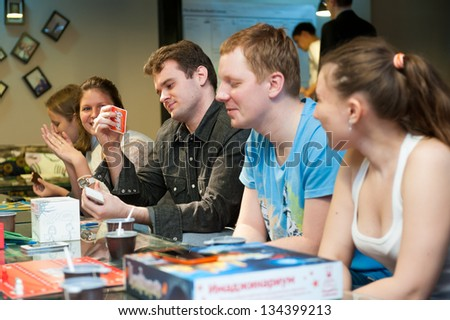 MOSCOW - APRIL 6: Unidentified young people playing Alias game on April 6, 2013 in Moscow. This game is becoming more and more popular among young people to relax in a cafe. - stock photo