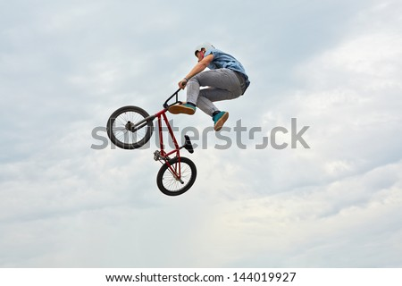 MOSCOW - AUG 4: Boy jumps on bike at All-Russian Exhibition Centre during holiday dedicated to 73d birthday of country main exhibition, August 4, 2012, Moscow, Russia. - stock photo