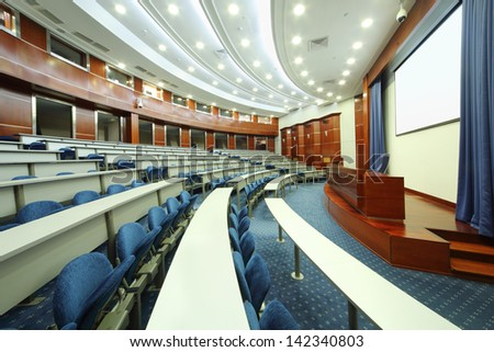 MOSCOW - AUGUST 18: Desks, blue seats, wooden rostrum in audience in MGIMO, on August 18, 2012 in Moscow, Russia. Moscow For 60 years, University has issued 30000 professionals. - stock photo