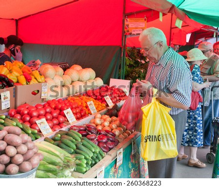 MOSCOW - AUGUST 08: Senior man buying vegetables in Vegetable Fair on Leskov Street on August 8, 2014 in Moscow. - stock photo