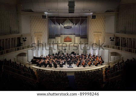 MOSCOW - FEB 26: Audience looks at Symphony Orchestra of Moscow State Conservatory named after P. Tchaikovsky in Tchaikovsky Concert Hall, Feb 26, 2011 in Moscow, Russia. Conductor is Anatoly Levin. - stock photo