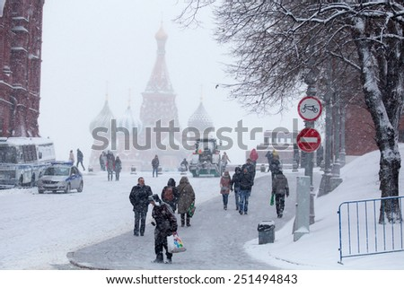 MOSCOW - FEBRUARY 03: People on winter and stormy Red Square and Cathedral of Saint Basil the Blessed is behind, February 03, 2015, Moscow, Russia  - stock photo