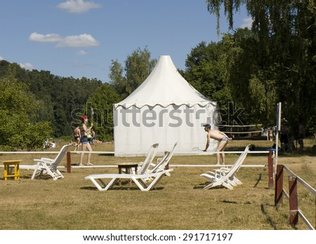 MOSCOW - JULY 20, 2014: people play badminton on beach in Serebryany bor (Silver forest) on Moskva-river, one of the most popular beaches of the city. - stock photo