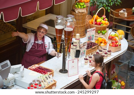 MOSCOW - JULY 29: The seller of fruits, juices and soft drinks talking with the buyer to the GUM store on July 29, 2014 in Moscow. - stock photo
