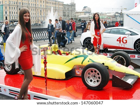 MOSCOW - JULY 20: Young models pose by sport cars at Moscow City Racing. Formula 1 teams show in historical city center of Moscow. Taken on July 20, 2013 in Moscow, Russia.  - stock photo