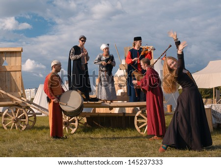 "MOSCOW - JUNE 23: Folk musicians and dancer performance at the Historical Festival ""The Times and Epoch"". Festival is dedicated to the period of the Middle Ages, on June 23, 2013 in Moscow, Russia. - stock photo"