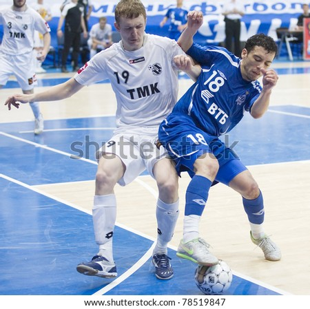 MOSCOW - JUNE 2, Russian Futsal championship, play-off games Dinamo vs. Sinara, final on June 2, 2011 in Moscow. Fernando (Dinamo) is struggling for a ball against Agapov (Sinara) - stock photo