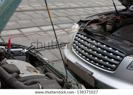 MOSCOW - MAR 19: Infiniti fx35 jumpstart other car to start the engine on March 19, 2012 in Moscow, Russia. According to the company Consumer Reports Japanese cars most reliable. - stock photo