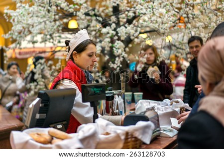 MOSCOW - MARCH 22: A buyer choosing a baking in the GUM store on March 22, 2015 in Moscow. GUM is the large store facing Red Square. It is popular among international tourists. - stock photo