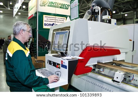 MOSCOW-MAY 18: Man operates woodworking machine with CNC at the international exhibition of professional furniture EEM Euroexpofurniture on May 18, 2011 in Moscow - stock photo