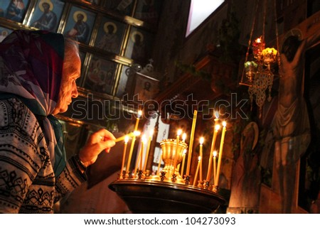MOSCOW-MAY 3: Old woman lights a prayer candle at the celebration of a Holy Trinity (Pentecost) by the church of St. Nicholas May 3, 2012 in Moscow - stock photo