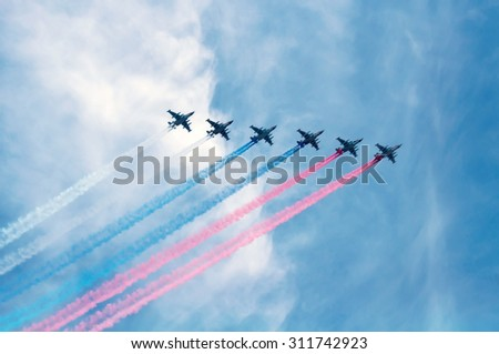 MOSCOW - MAY 9, 2015: Six aircrafts make tricolor smoke during military parade on anniversary of Victory in World War II - stock photo