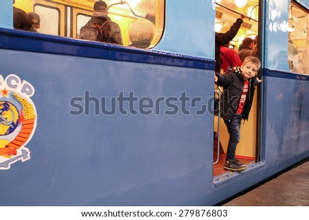 MOSCOW - MAY 5, 2015: Unidentified child looks vintage subway car at the exhibition of retro-cars dedicated to the 80th anniversary of the Moscow Metro. Public-event - stock photo