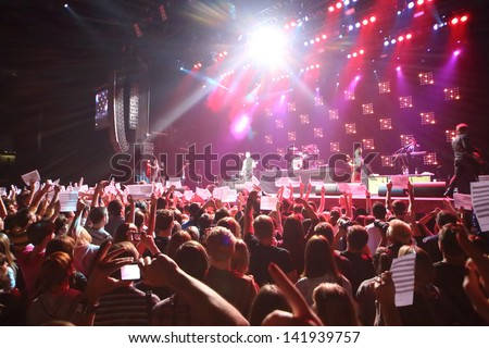MOSCOW - OCT 12: Spectators hold American flags on DAUGHTRY group performs on stage of Stadium Live on October 12, 2012 in Moscow, Russia. - stock photo