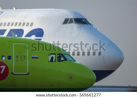 Moscow region, Domodedovo, Russia - July 07, 2014: Boeing 747-400 Transaero airlines and Airbus A320 S7 Siberia airlines standing at Domodedovo international airport - stock photo