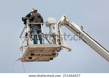 MOSCOW REGION, SERGIYEV POSAD, RUSSIA- JUL 18, 2014:  Videographer produces video report from the height of a crane on a celebration of the 700th anniversary of the birthday of St. Sergius of Radonezh - stock photo