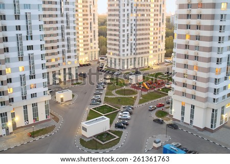 MOSCOW, RUSSIA - APR 23, 2014: Courtyard with tall buildings, parking and playgrounds in modern residential complex Elk Island in the evening, top view - stock photo