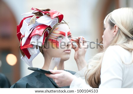 """MOSCOW, RUSSIA-FEBRUARY 11: Stylist and model prepare on the IX Open Championship for creative makeup KOSMETIK international on February 11, 2012 in Moscow, Russia. Theme """"Photoshoot. Face of future�» - stock photo"""