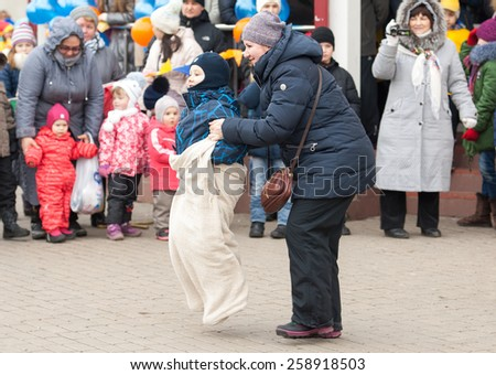 MOSCOW, RUSSIA - FEBRUARY 22: Unidentified woman with boy running on Russian religious and folk holiday Maslenitsa near Culture center Peresvet on February 22, 2015, Russia - stock photo